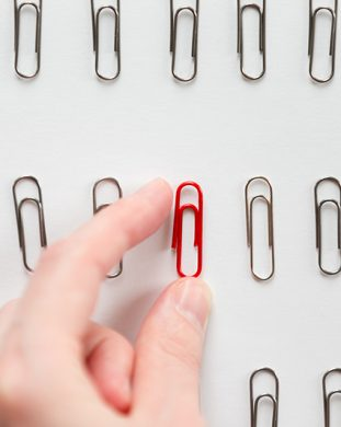 Hand picking among metal paperclips one red, different from the others, isolated on white background. Stand out from the crowd concept, high angle